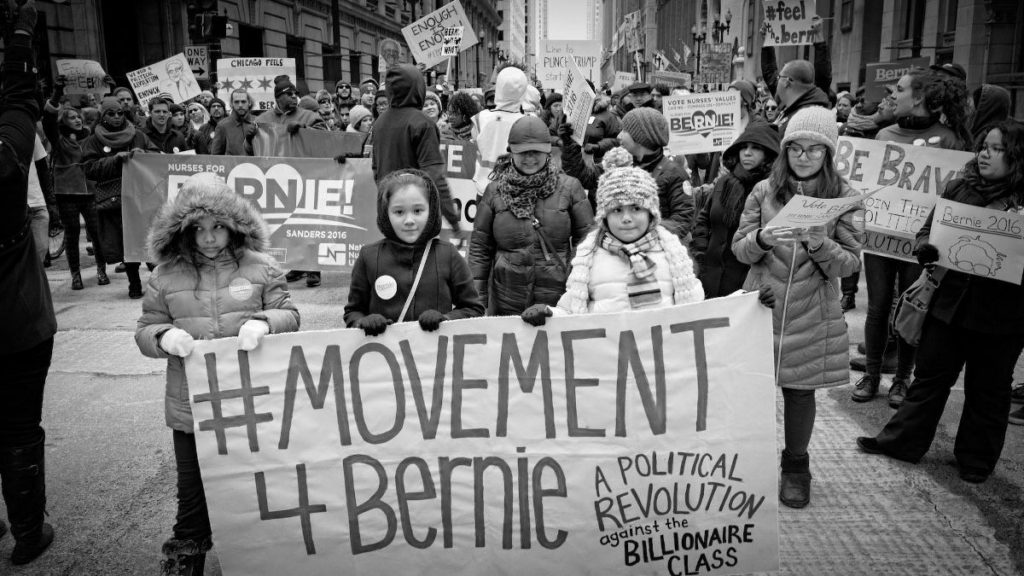 """black and white photo of marchers holding a banner that reads """"#movement4bernie"""""""